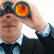 Young business man looking through binocular - Stock Photo