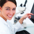 Closeup of a happy beautiful business woman at desk using comput - Foto Stock