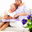 Smiling mother and daughter sitting together - Stockfoto