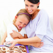 Smiling girl and mother sitting together on sofa with chocolates - Stockfoto