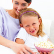 Happy mother and daughter sitting together with popcorn at home - Stockfoto