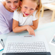 Royalty-Free Stock Photo: Portrait of smiling girl sitting with her mother, using laptop