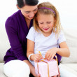 Smiling young woman with her daughter opening gift - Стоковая фотография