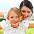 Happy young mother playing with her daughter - Stock Photo