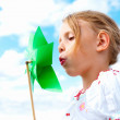 Royalty-Free Stock Photo: Pretty young girl blowing pinwheel