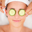 Closeup of cucumber slices on a smiling young girl's eyes - Stock Photo