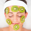 Royalty-Free Stock Photo: Closeup of kiwi slices on a young girl\'s face