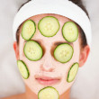 Closeup of cucumber slices and facial mask on a young girl&#039;s fac - Stock Photo