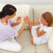 Mother and daughter playing clapping game - Stockfoto