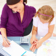 Mother on phone while writing notes by daughter drawing at desk - Stockfoto