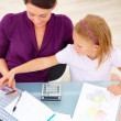 Young mother and daughter sitting by desk and looking at mobile - Stockfoto
