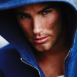 Portrait of a rough and sexy model wearing a blue hoodie - Stock Photo