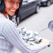 Closeup of a happy woman riding a motorcycle on the street - Foto Stock