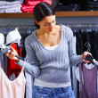 Young lady purchasing clothes in store - Lizenzfreies Foto