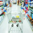 Shopping cart in aisle of supermarket - Stock Photo