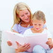 Mother with her cute daughter reading a book against white backg - Stock Photo