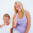 Royalty-Free Stock Photo: Mother and daughter brushing their teeth against white backgroun