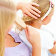 Closeup of a mother combing her daughter&#039;s hair - Stock Photo
