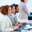 Royalty-Free Stock Photo: Young executives sitting with headsets and using laptop