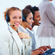 Royalty-Free Stock Photo: Closeup of young executives sitting with headsets and using lapt