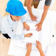 Royalty-Free Stock Photo: Top view of female architect with colleagues working on blue pri