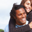 Royalty-Free Stock Photo: Young man carrying young woman on his back