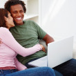 Royalty-Free Stock Photo: Smiling couple sitting with a laptop on a sofa
