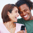 Royalty-Free Stock Photo: Happy smiling couple using a cellphone against white