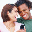 Royalty-Free Stock Photo: Laughing young couple holding mobile phone