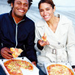Young man and woman eating pizza outdoors - Stock Photo