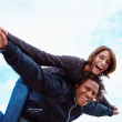 Royalty-Free Stock Photo: Young man giving piggyback to woman against sky