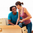 Smiling couple packing in their new house - Stock Photo