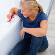 Happy young woman sitting and painting - Stock Photo