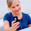 Closeup of a cute young girl with earphones and laptop holding a - Stock Photo