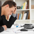 Stressed young man at home desk - Stock Photo