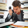 Closeup of a young angry business man shouting over a telephone - Stock Photo