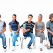 Bored modern students sitting on chairs - Foto Stock