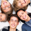 Happy teens smiling and lying on white floor - Stok fotoğraf