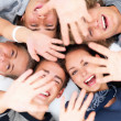 Royalty-Free Stock Photo: Happy young friends lying down giving high five