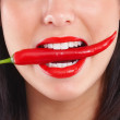 Royalty-Free Stock Photo: Closeup of young girl with red chilli in mouth