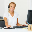 Royalty-Free Stock Photo: Serveice woman wearing headset using a computer