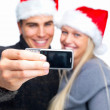 Christmas - Taking a portrait of a young couple - Stock Photo
