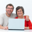 Happy mature couple using  laptop white background - Stock Photo