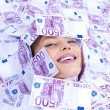 Royalty-Free Stock Photo: Woman lying covered with money on the floor