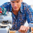 Royalty-Free Stock Photo: Handy man using a bench saw at work