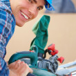 Happy handy man at work using Table saw - Stock Photo