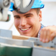 Happy young carpenter at work lining up his cut - Stock Photo