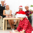 Young child opening her presents under the christmas tree - Stock Photo