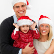 Festive young couple holding their daughter at christmas - Stock Photo