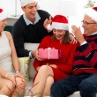 Portrait of a festive  family opening christmas gifts - Stock Photo